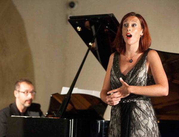 Female singer in a recital dress by a piano