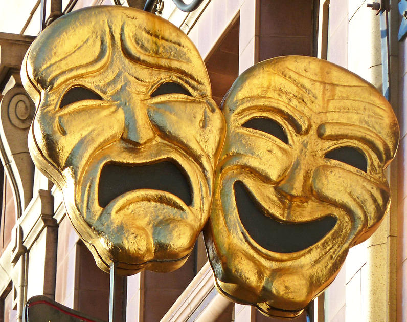 comedy and tragedy masks hanging outside a theater
