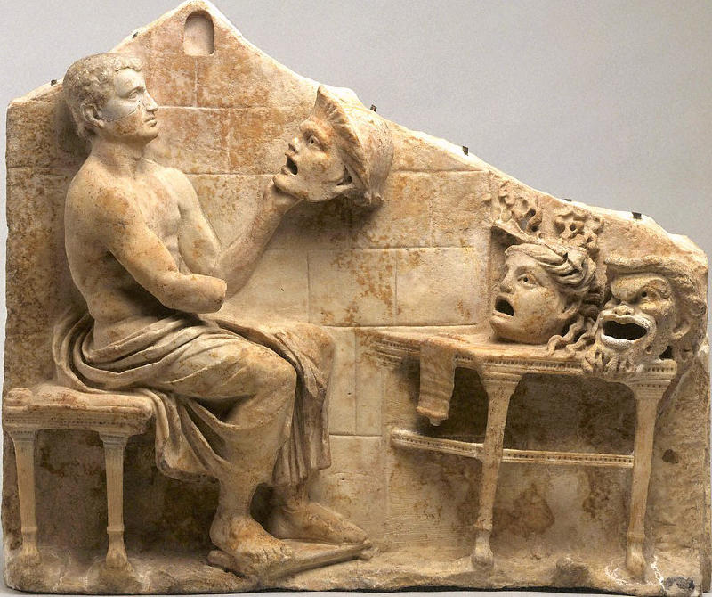 stone carving of an ancient Greek actor and drama masks